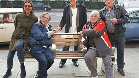 "The new Honeycombs line-up on the ""Meek bench"" in Holloway Road, which has a plaque commemorating th"