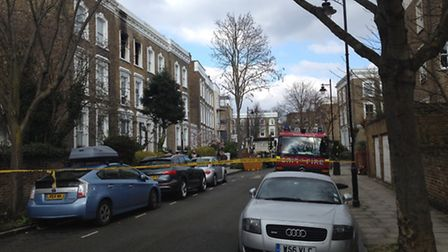 Crowland Terrace, Canonbury, was still cordoned off with hazard tape this afternoon. The woman's fla