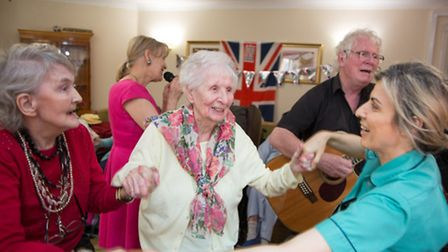 Pauline Peatty (white cardigan) and Rosemary Walsh dance with Senior Care Assistant Irina Remiera at