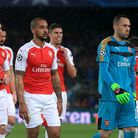 The Arsenal players leave the field dejected after the final whistle beyond Barcelona's Lionel Messi