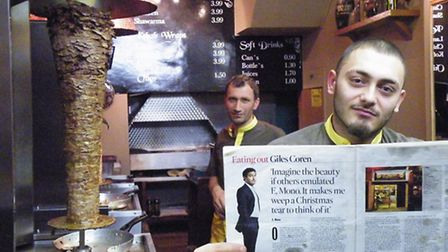 Michael Ustun's son Jibril holds up a copy of Giles Coren's rave review