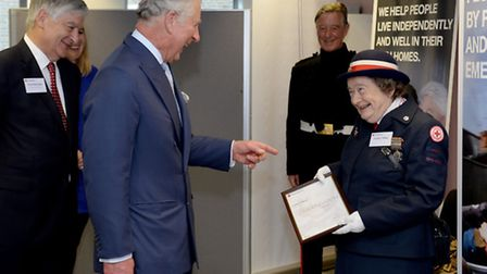 The Prince of Wales presents a certificate of recognition to fund raising volunteer Audrey Tibbles,