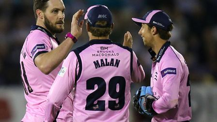 Mitch McClenaghan (left) celebrates the wicket of Essex's Callum Taylor with team-mates Dawid Malan