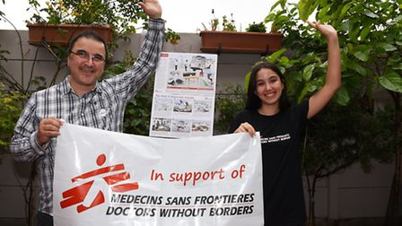Betul and her father with a banner from charity MSF (Picture: Ken Mears)