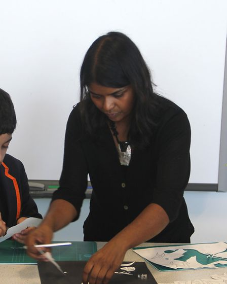 Artist Sarah Pimenta helping one of the children with their artwork