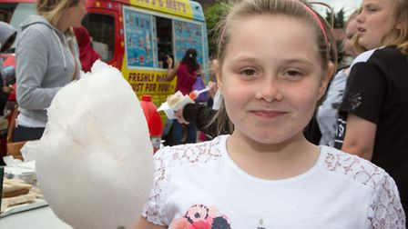 Chelsea Ormston, 9, enjoys a candy floss at the Kingsbury Primary School fete Pic credit: Jonathan