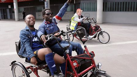 Emmanuel Nmecha, 17 (left) riding a two seater bike with support worker Harold Bennett during a disa