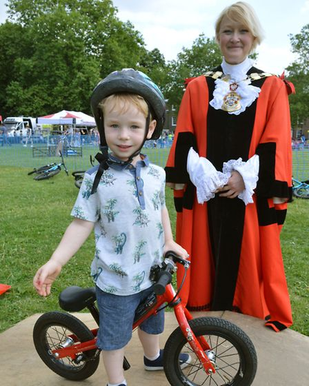 Three-year-old Robin Jenkins tries out his BMX skills at Go Islington in Highbury Fields. He is watc