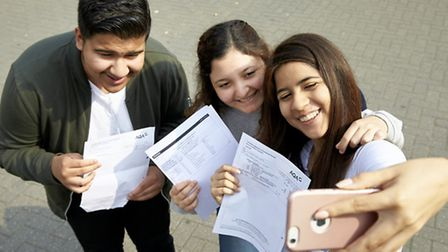 Students pose for photos following their results