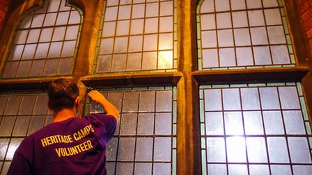 A volunteer get to cleaning the windows at the Chapel
