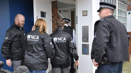 NCA officers arriving at Markuta's home to arrest him (Pic: NCA)