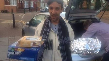 Carlos, from Ashford Place homeless centre, carries in cakes donated by Mulberry House School in Wes