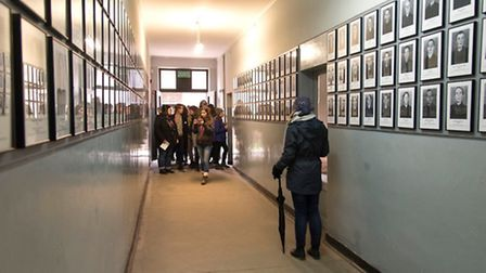 Students walk through the corridor in Auschwitz I covered with pictures of inmates Picture: grah