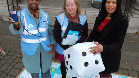 Volunteer Lawrencia Frempong, left, holds an air pollution monitor with volunteer Tiia Haataja, cent