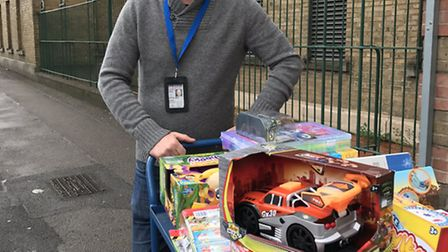 Pc David Williams receives 80 gifts from Finsbury Park's Toy Project charity - with 20 more close be