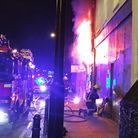 Flames burst out of a window at the hair salon. Picture: Catherine Bethune