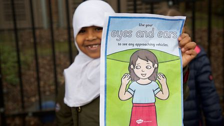 A pupil with her road awareness poster