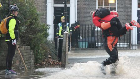 Firefighters carry victims of the Upper Street flooding to safety.