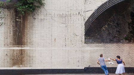 Two people exchanging a teddy bear under a bridge by the Emirates Stadium. Photographer Josh Redman: