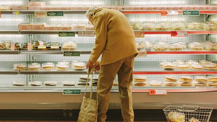 A woman in Morrisons, Holloway. Photographer Josh Redman: 'She was picking up each cake and looking