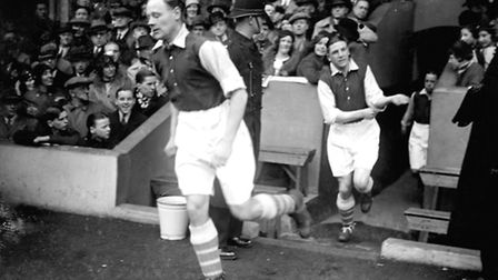 Arsenal legend George Male, running onto the Highbury pitch in 1934, was one of the first players to