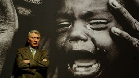 Photographer Don McCullin stands in front of one of his war photos at an exhibition in 2010. Picture