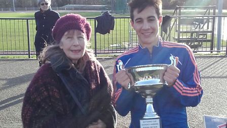 Highgate Harriers' Aurel Sinko-Uribe (right) receives the annual Bottomists Trophy from Pam Fosbrook