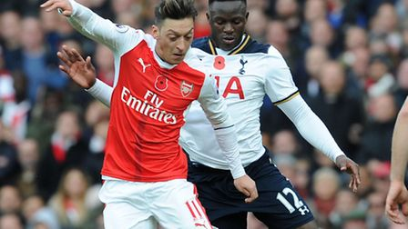 Arsenal's Mesut Ozil and Tottenham's Victor Wanyama tussle during the derby game where poppies were