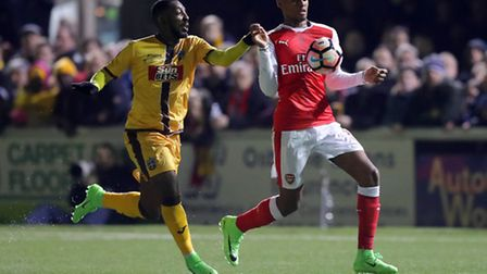 Sutton's Roarie Deacon and Arsenal's Jeff Reine-Adelaide battle for the ball during their Emirates F