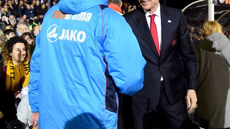 Sutton United's manager Paul Doswell (left) and Arsenal manager Arsene Wenger shake hands before the