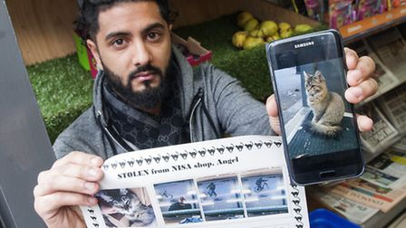 Nisa in Islington had its pet cat Bella stolen.Pictured, shop owner Haseeb Kashmiri with a photogr