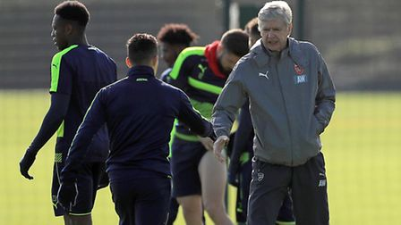 Arsenal's Alexis Sanchez (left) shakes hands with Manager Arsene Wenger (centre) during a training s