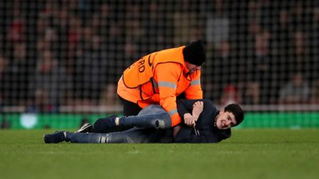 A pitch invader is tackled during the UEFA Champions League Round of 16, Second Leg match at the Emi