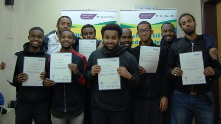Delighted construction skills certificate scheme course graduates showcasing their certifcates.