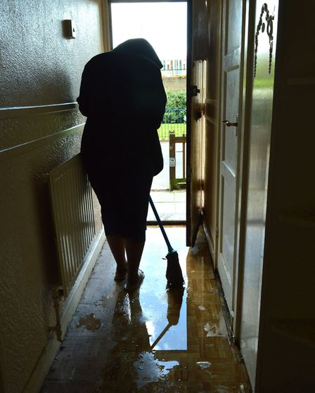 Kike Ogunseye mops floor in her flat at Colley House Hilldrop Estate. Picture: Polly Hancock