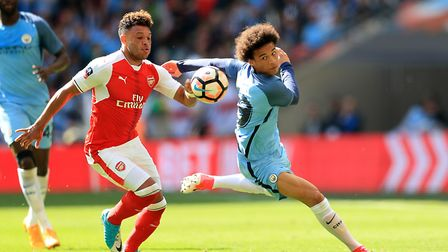Arsenal's Alex Oxlade-Chamberlain (left) and Manchester City's Leroy Sane battle for the ball during