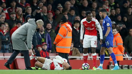 Arsenal manager Arsene Wenger attends to Alexis Sanchez during the Premier League match at the Emira