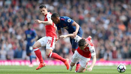 Arsenal's Laurent Koscielny (right) and Manchester United's Anthony Martial (centre) battle for the
