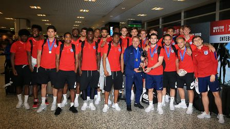 The England U20s squad and manager Paul Simpson pose with the World Cup after their arrival back at