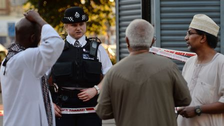 A police officer talks to neighbours at the scene of the terror attack this morning. Picture: Victor