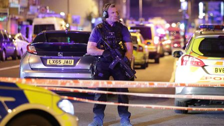 An armed police officer mans a cordon on the Seven Sisters Road after the attack that injured at lea