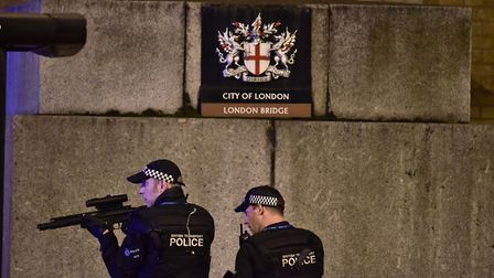 Armed Police officer looks through his weapon on London Bridge as police are dealt with a suspected