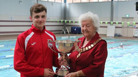 Islington Anaconda swimmer Tommy Donovan receives the Alan Lawrence Memorial Trophy from Middlesex A