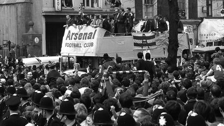 Arsenal's Frank McLintock holds the European Fairs Cup aboard an open-top bus in Upper Street on the