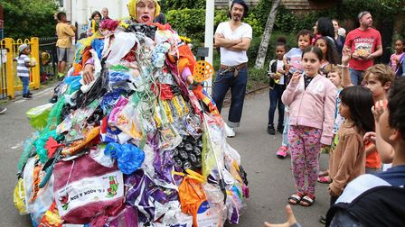 A woman dressed in plastic bags entertains children and warns about global warming at Whitecross Str