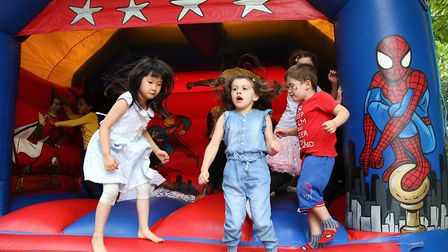 Ningyi, five, with schoolfriend Milly Atkin, five, on the bouncy castle at Whitecross Street Party o