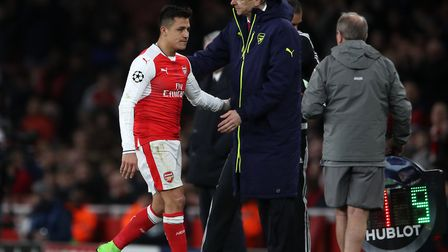 Arsenal's Alexis Sanchez walks by manager Arsene Wenger after being substituted during the UEFA Cham