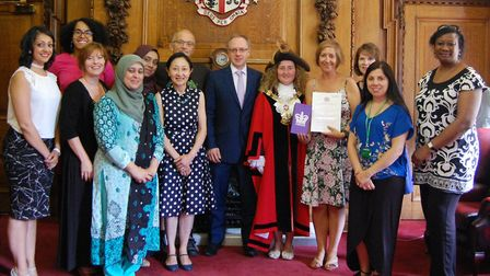 The Parent House is congratulated by Islington Council leader Richard Watts, cente, for its Queen's