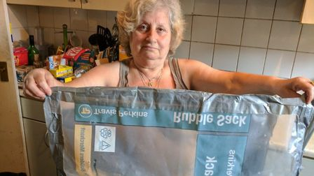 Panayiota Christou with the Travis Perkins sack used to cover over the enormous hole in her shower w