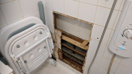 The hole in Ms Christou's shower wall, which gaped for six weeks before someone covered it over with